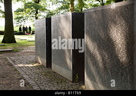 Names of war dead with statues in distance Deutscher Soldatenfriedhof German war cemetery Belgium - Stock Photo