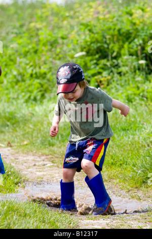 Boy splashing in a muddy puddle - Stock Photo