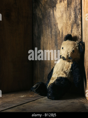Old teddy bear in wooden box - Stock Photo