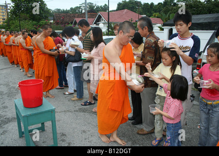 Buddhist monks receiving alms from devotees - Stock Photo