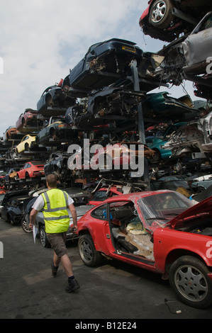 High performance expensive Porche porsche motor cars stacked up in a scrap yard awaiting breaking down for spare - Stock Photo