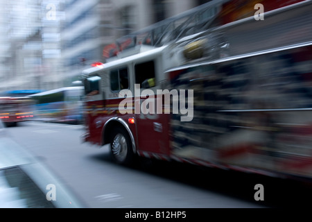 An FDNY truck rushes to the scene of an emergency in Manhattan, NY. - Stock Photo