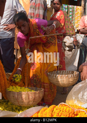 weighing flowers at the Malik Ghat flower market in Calcutta - Stock Photo