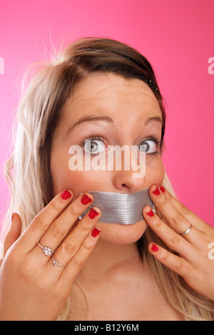 Teenage girl pressing gaffer tape over her mouth - Stock Photo