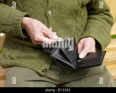 old hands of a senior counting less money in a purse - Stock Photo