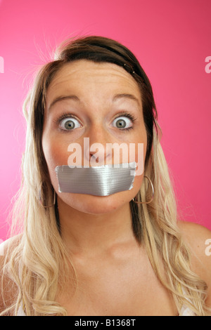 Teenage girl with gaffer tape over her mouth and a wide eyed expression. - Stock Photo