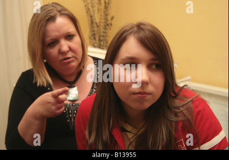 Mother telling off teenage daughter but being ignored - Stock Photo