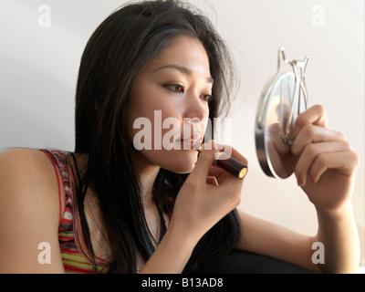 Young Asian women applying lipstick. - Stock Photo