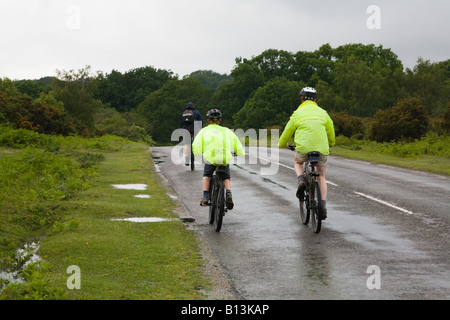 Family cycling on a country road. Holiday season. Wet miserable day in the New Forest, Hampshire, UK. - Stock Photo