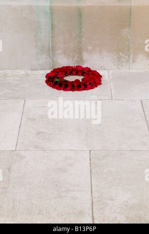 A single poppy wreath at the base of a war memorial on rememberance Sunday - Stock Photo