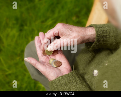 old hands of a senior counting less money, coins - Stock Photo