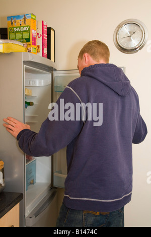 Young Millennial man looking into a refrigerator with open door in domestic kitchen at lunch time England Britain UK Stock Photo