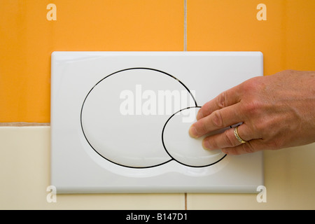 Dual toilet flush with hand pressing small economy flush button in public convenience WC. England UK Britain - Stock Photo
