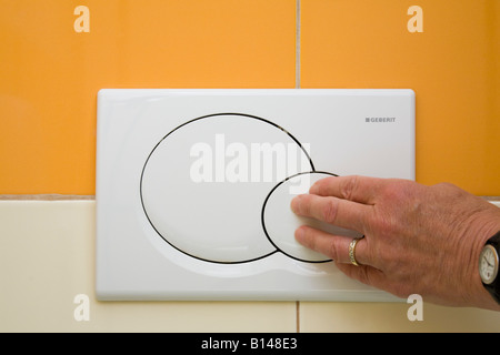 Toilet flush with person's hand pressing dual small economy flush button on tiled wall in public convenience WC - Stock Photo