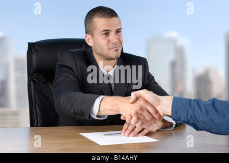 Businessman shaking hands with a client - Stock Photo