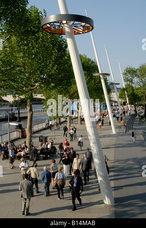 People walking and enjoying the late afternoon sun on London's South Bank, beside the River Thames, London, England - Stock Photo