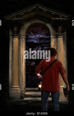 A man discovers an ornate doorway in an underground cave. - Stock Photo