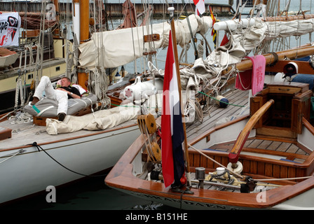 Sailing Yachts Yarmouth Isle of Wight England Festival of the Seas One crew member takes a nap on deck - Stock Photo