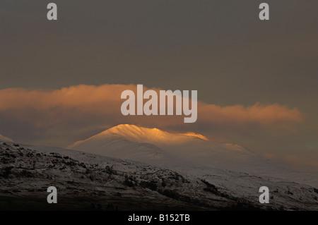 The last rays of evening sun illuminate the snowy summit of Beinn Ghlas in an orange glow Ben Lawers range Perthshire - Stock Photo