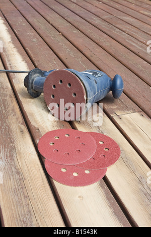 Random orbital sander lying on its side showing sanding disk and spares on partially sanded wooden decking during - Stock Photo