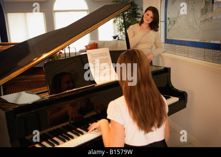 Teenage daughter playing the piano for her mother - Stock Photo