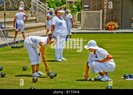 Wearing the regulation white uniforms two woman players measure the distance between two lawn bowling balls at competition - Stock Photo