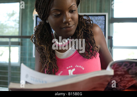 Young black girl reads journal - Stock Photo