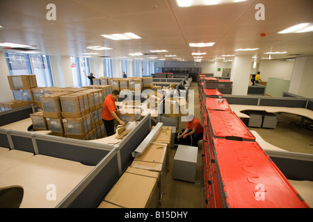 Workmen unpack new filing cabinets while outfitting a newly constructed office building. - Stock Photo
