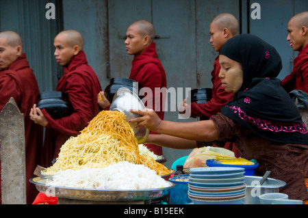 Buddhist monks pass a food stall on their way to their morning alms walk in the center of Yangon Myanmar, Burma - Stock Photo
