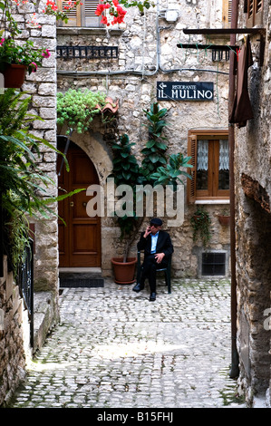 Old man sitting in front of his house in Sermoneta, Italy - Stock Photo