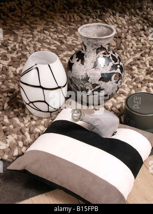 Combining trendy modern interior items in brown grey earth colours vases carpet light pillow - Stock Photo