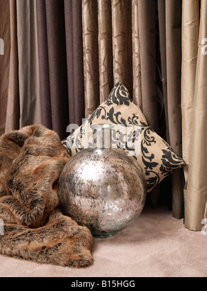 Combining trendy modern interior items in brown grey earth colours vase fur drapes curtains pillow - Stock Photo