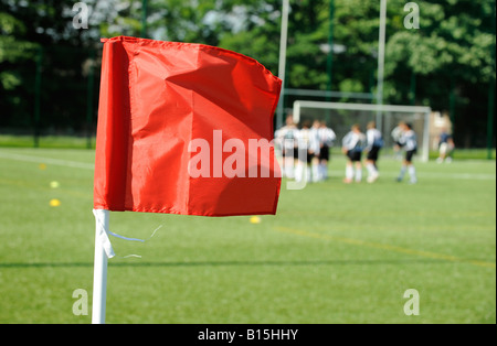 A bright red flag waving in foreground with blurred football players in background on artificial turf football pitch. - Stock Photo
