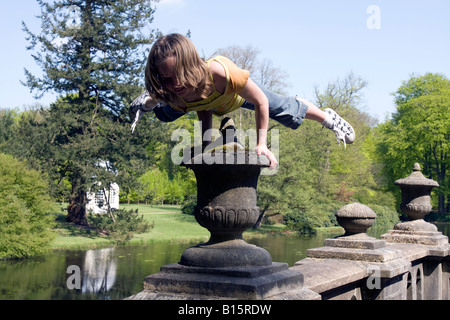 Eight year old blond girl performing acrobatic gymnastics on a vase in the garden of castle 'the old Loo', Apeldoorn,Netherlands - Stock Photo
