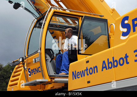 The crane driver in his digitalized cab where a computer system controls 95 of his actions - Stock Photo