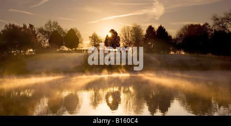 Sunrise, dawn on a misty, frosty autumn, winter morning, mist rising from the laken at Coate Water Country Park, - Stock Photo