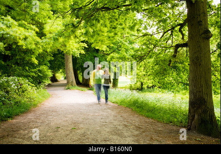 Couple walking arm in arm along a leafy path in dappled summer sunshine at Coate Water Country Park, Wiltshire, - Stock Photo