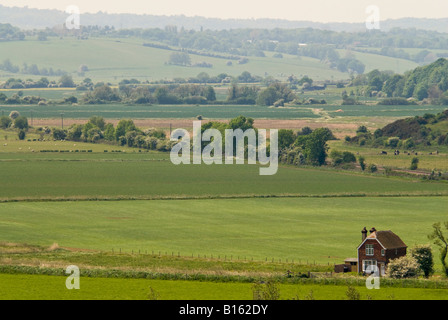 Horizontal aerial view over the green countryside and rolling hills of East Sussex on a sunny day. - Stock Photo