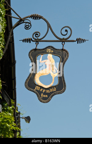 Vertical close up of an old black wrought iron pub sign suspended outside a Tudor building in Rye on a sunny day. - Stock Photo
