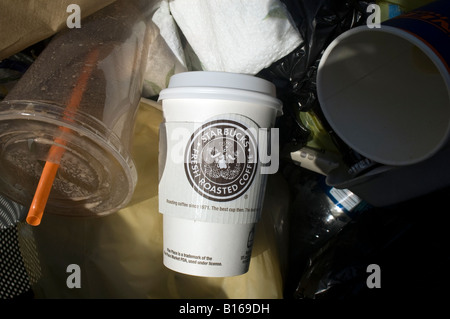 Starbucks coffee cup showing new logo in the trash - Stock Photo