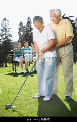 Senior Asian couple playing golf - Stock Photo