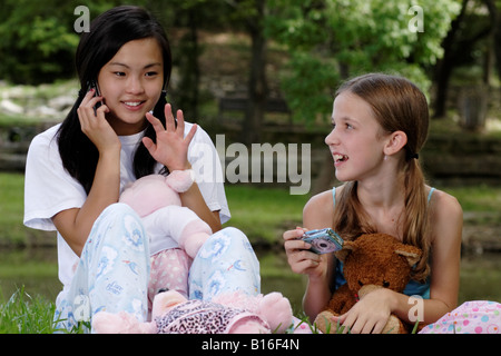 Stock Photograph of a girl talking on a cell phone while another gets ready to take a picture - Stock Photo