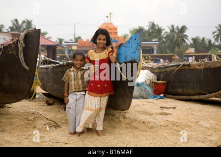 Two children grin for the camera on Kappil Beach in Kasaragod, Kerala. Fishing boats are pulled up on the beach - Stock Photo