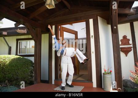 African man carrying wife in doorway