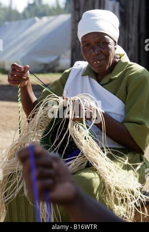 Kenya: Woman weaving baskets, refugee camp SHOW GROUND in Eldoret, Rift Valley - Stock Photo