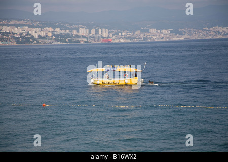 Opatija Istria Croatia Europe May The Glass boat water taxi with the owners dog being towed on the surfboard - Stock Photo