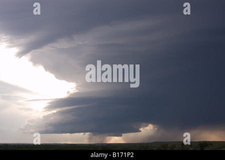 Evening cumulonimbus clouds with developing thunderstorm and rain with small funnel cloud in cumulus clouds in center - Stock Photo