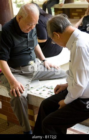 Men Playing Chinese Chess in Park in Kowloon Hong Kong - Stock Photo