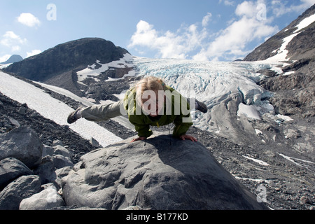 Eight year old blond girl performing acrobatic gymnastics in front of glacier at Jotunheimen in Norway - Stock Photo