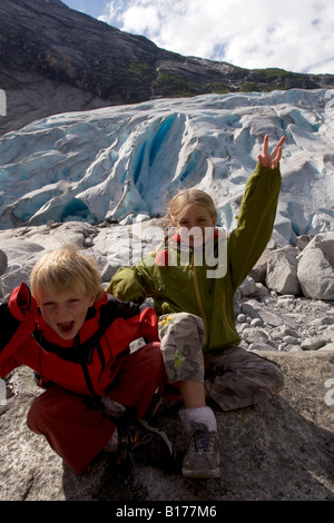 Blond brother and sister making funny faces to the photographer in front of Nigardsbreen, Nigard, Jostedalen, Norway - Stock Photo
